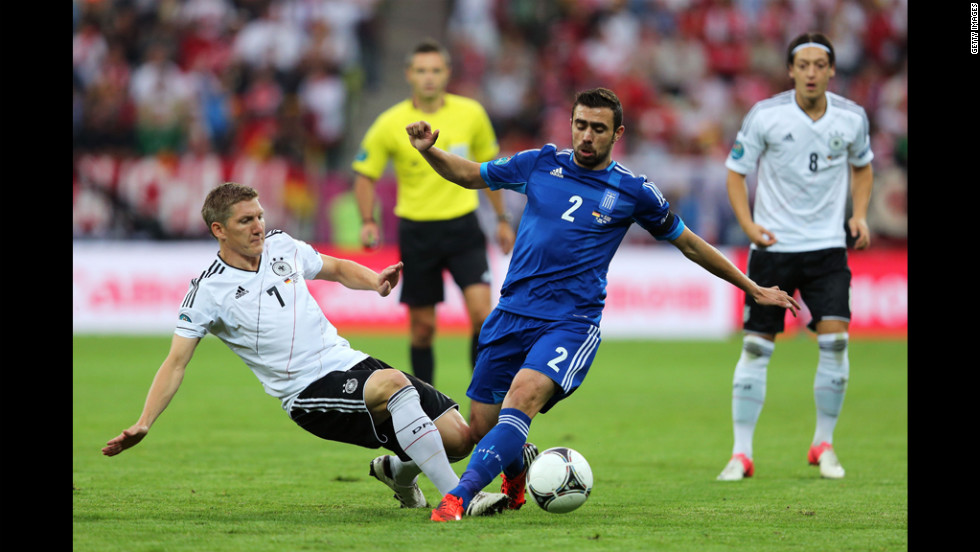 Germany's Bastian Schweinsteiger, left, tackles Giannis Maniatis of Greece.