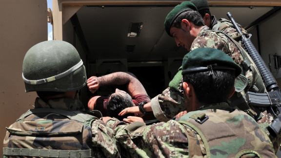 Afghan soldiers remove the body of a civilian after the standoff ended. Militants killed 15 civilians, a police officer and three security guards, according to authorities.