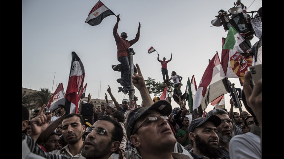 Protesters wave flags and shout slogans in Tahrir Square on Friday, June 22, in Cairo.