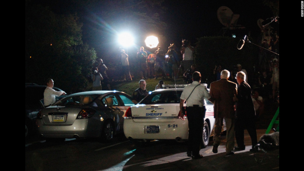 Sandusky is escorted in handuffs to a police car at the Centre County Courthouse under the glare of TV lights. The jury found Sandusky guilty on 45 of 48 counts.