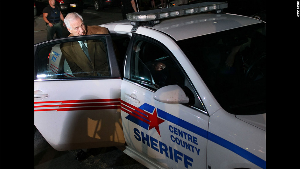 Sandusky is put into a police car.
