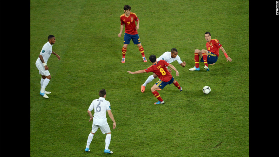 Xavi of Spain challenges Florent Malouda of France.