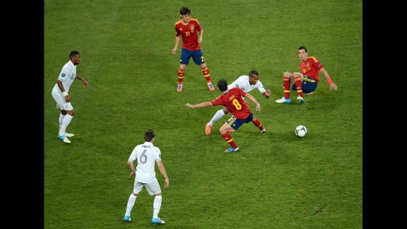 Xavi of Spain challenges Florent Malouda of France.