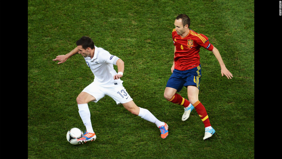 Anthony Reveillere of France is closed down by Andres Iniesta of Spain.