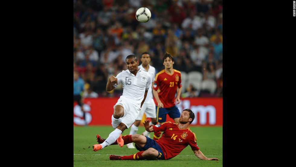Xabi Alonso of Spain challenges Florent Malouda of France during the quarter final match between Spain and France.
