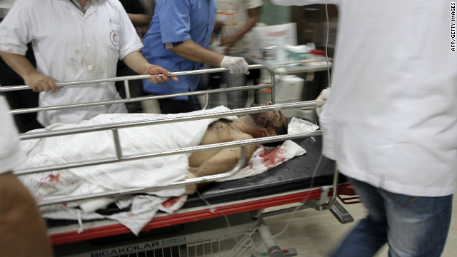 Palestinian medics tend to a man wounded during Israeli air strikes in Gaza on June 23, 2012.