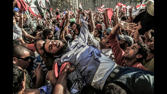 A supporter of the Muslim Brotherhood is carried away from the tightly packed arena of Tahrir Square in Cairo on Sunday as Mohamed Morsi supporters celebrate his victory in Egypt