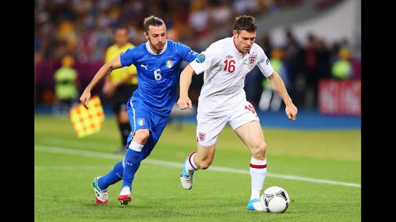 Federico Balzaretti of Italy runs after James Milner of England.