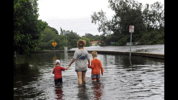 Angela Kelly and her sons Ethan, 3, and Alex, 6, check out flooding damage in their St. Petersburg-area neighborhood Monday, June 25. Isolated parts of Florida could see 25 inches of rain from Debby.