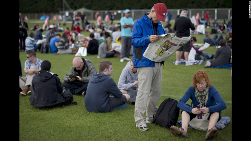 Tennis fans pass the time as they wait in line for tickets outside the stadium June 26.
