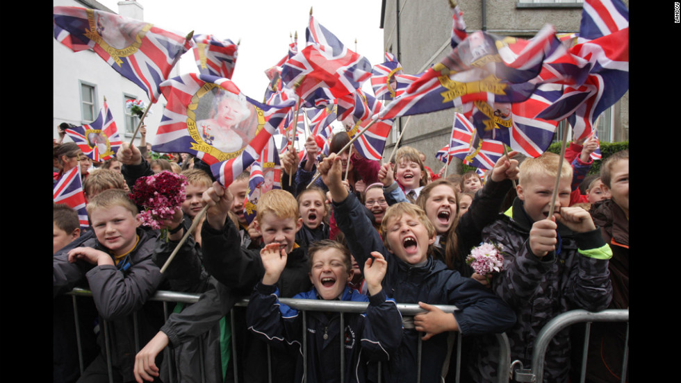 Crowds wave Union flags Tuesday in Enniskillen, Northern Ireland, as they wait for the arrival of Queen Elizabeth II.
