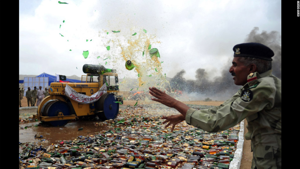 A Pakistani soldier in Karachi destroys seized bottles of liquor during a ceremony Tuesday to mark International Day against Drug Abuse and Illicit Trafficking.