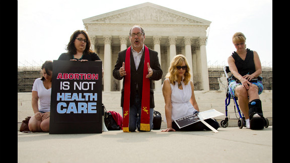 The Rev. Patrick Mahoney leads demonstrators in prayer outside the Supreme Court on Monday, June 25, as they await the court