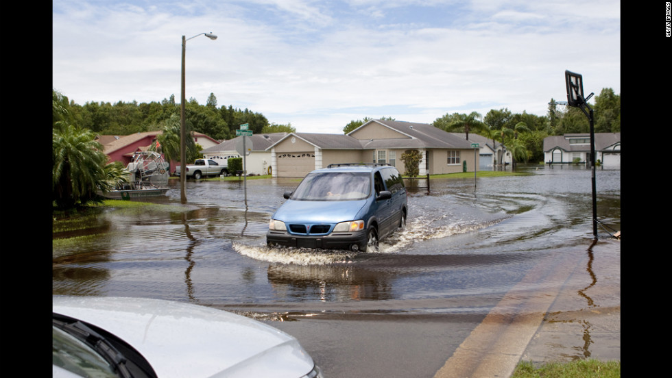 A car drives on a flooded street on Tuesday, June 26, in New Port Richey, Florida. Residents are preparing to leave under a mandatory evacuation order. According to local reports, two area rivers have converged and surpassed the 100-year flood plain.