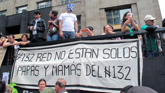 """Parents of student protesters display a sign supporting the youth movement known as #YoSoy132. """"You are not alone,"""" it says."""