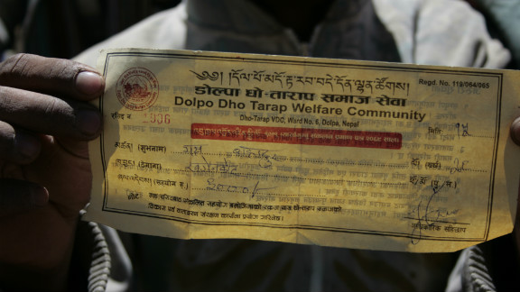 A harvester holds up his tax receipt. Citizen committees in Dolpa levy taxes on migrant harvesters in an effort to buoy the local economy and fund environmental clean-up activities.