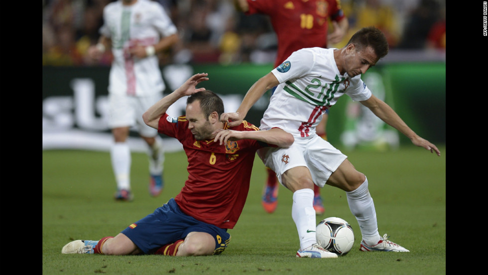 Spanish midfielder Andres Iniesta, left, falls while vying with Portuguese defender Joao Pereira.