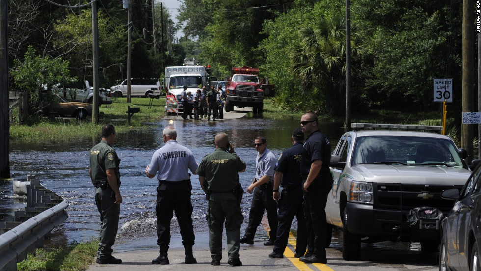 Emergency crews work the scene of a flooded street, where Pasco County Sheriff's Office Public Information Officer Doug Tobin confirms they are attempting to recover an unidentified body in New Port Richey, Florida, on Wednesday, June 27. Debby weakened to a tropical depression after it drifted ashore on Florida's Gulf Coast on Tuesday.