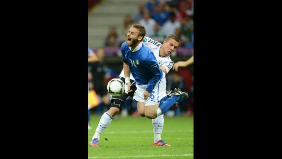 Italian midfielder Daniele De Rossi goes airborne past German forward Lukas Podolski on Thursday.