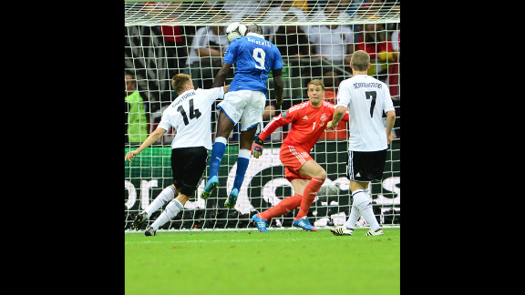 Italian forward Mario Balotelli, in blue, heads the ball into the goal, scoring the first goal in the match.