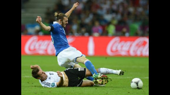 German forward Miroslav Klose lands on the ground while vying with Italian defender Federico  Balzaretti.