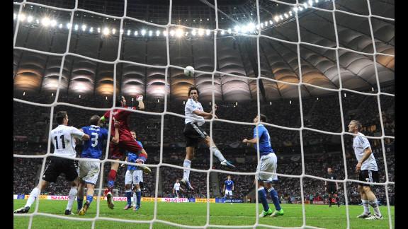 German defender Mats Hummels, center, heads the ball by Italian goalkeeper Gianluigi Buffon, in red.