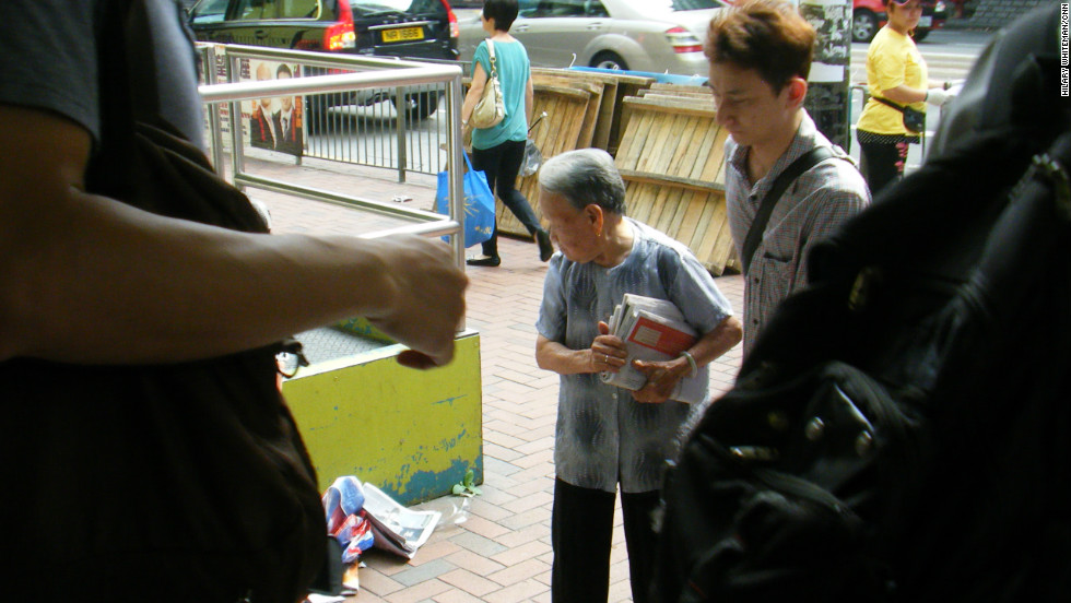 Life is hard for low income earners in Hong Kong as booming house prices push up the cost of rent. Outside metro stations, elderly women collect free daily newspapers discarded by commuters which they then sell to earn some money.