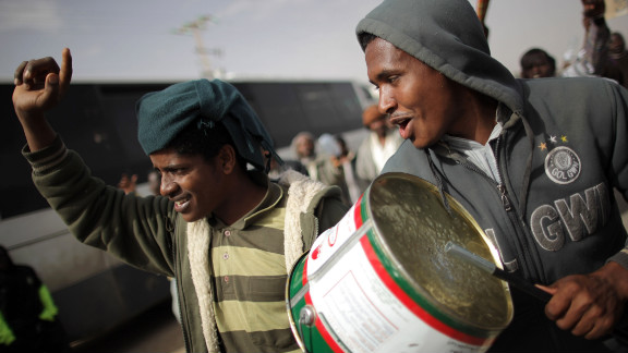 Sudanese men protest on the road through a United Nations displacement camp.