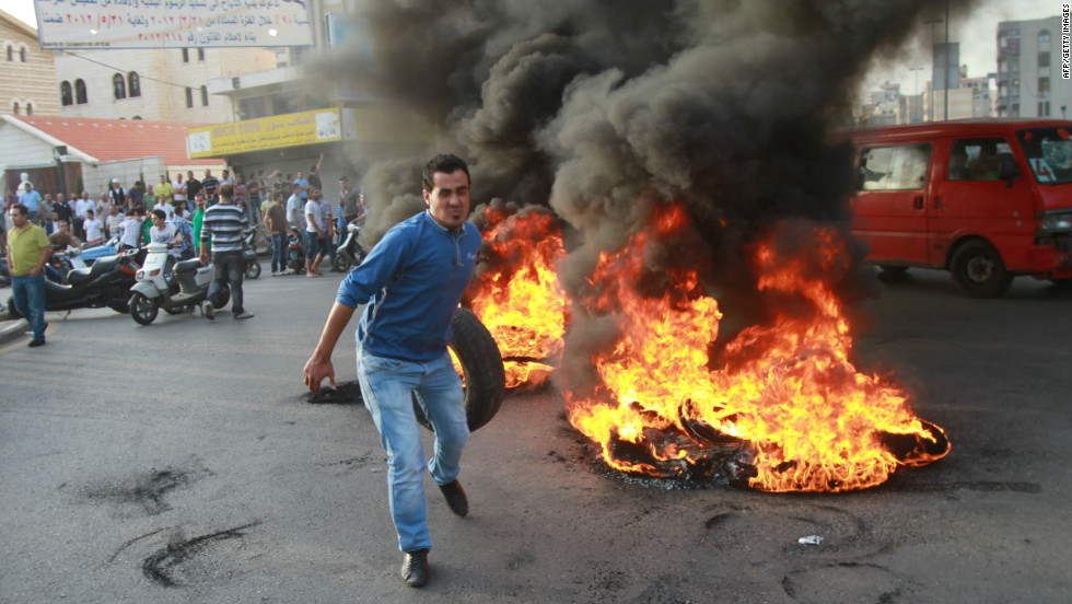 Car tires, piled and burned as roadblocks, have become a symbol of Lebanon's troubles. Pictured, youths set tires on fire in Beirut in protest against the kidnapping of Lebanese Shiite pilgrims in Syria, in May 2012.