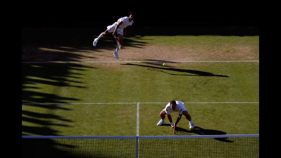Andre Sa serves over teammate Bruno Soares in the Brazilians