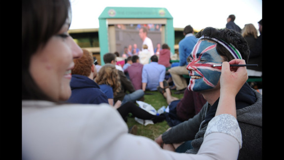 A spectator, Matt Griggs, right, has a Union Jack painted on his face by Kelsey Bennett, left, on