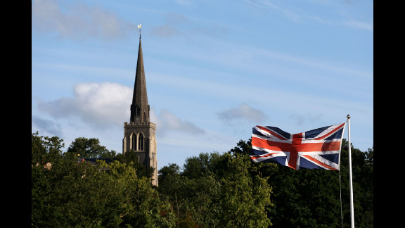 A Union Jack flaps in the breeze outside the All-England Club with the spire of St. Mary