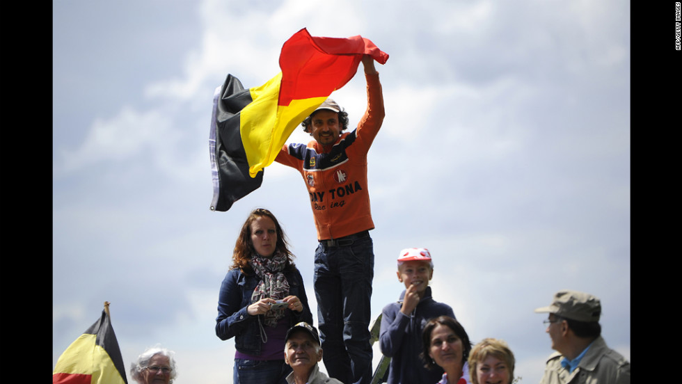 A spectator waves the Belgian flag as fans wait for riders to pass along the Stage 1 route on Sunday.