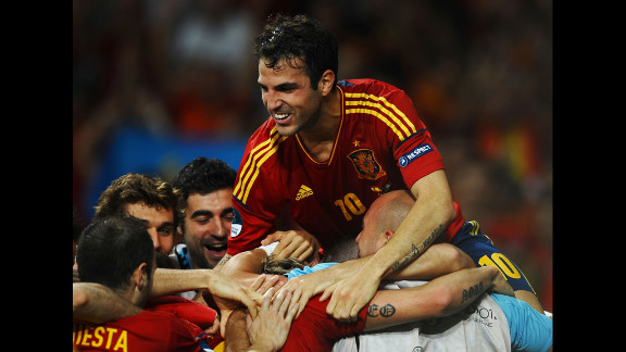 Cesc Fabregas of Spain jumps on his teammates as they celebrate after Fernando Torres scored his team