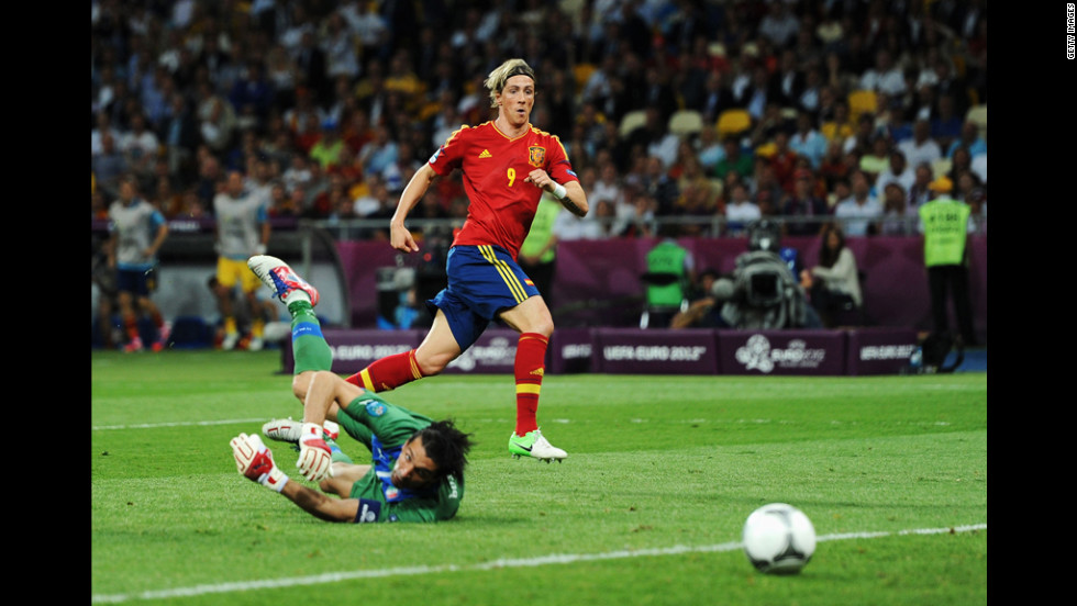Gianluigi Buffon of Italy looks back at the ball as Spain's Fernando Torres scores.