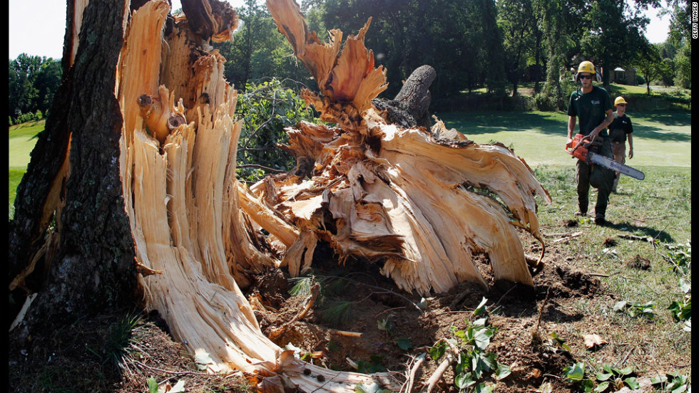 Workers cut up a tree along the 14th fairway from overnight storm damage that delayed the start of the third round of the AT&T National at Congressional Country Club in Bethesda, Maryland.