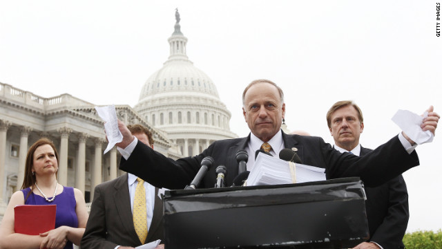 Rep. Steve King, R-Iowa, tears a page from the national health care bill at a March press conference.