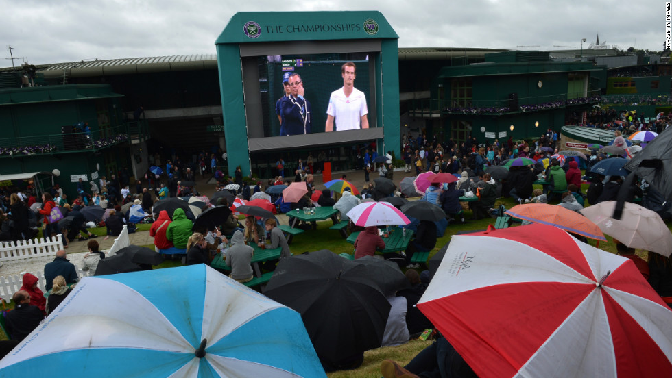 "Spectators take shelter under umbrellas on ""Murray Mount"" for the match between Britain's Andy Murray and Croatia's Marin Cilic."