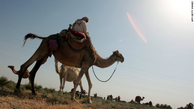 An Iraqi shepherd rides a camel in the Kut desert, about 180 kilometers south of Baghdad, on July 1, 2012, as he leads his caravan of camels on a trip across provinces looking for water and shrubs in a country hit by a wave of heat and drought. Iraq has suffered several droughts over the past decade -- to worsen an already difficult environmental situation, with sandstorms in Baghdad regularly forcing the closure of the capital's airport, and leading to increased hospital visits due to respiratory problems. AFP PHOTO ALI AL- SAADI (Photo credit should read ALI AL-SAADI/AFP/GettyImages)