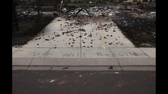 "The words ""We Will Rebuild"" are seen written on the sidewalk in front of a house in Colorado Springs that was destroyed by the fire."