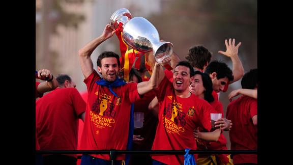 Juan Mata, left, and Santi Cazorla of Spain hoist the Euro 2012 trophy during Monday