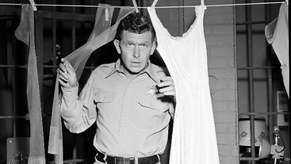 """Griffith as Sheriff Andy Taylor peers through laundry in """"Andy and the Woman Speeder."""""""