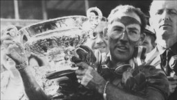 Stirling Moss lifts the trophy at the British Grand Prix in 1955.