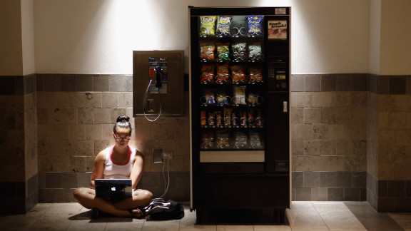 Katie Kiang finds shelter from the heat to study for the Graduate Record Examinations inside an air-conditioned mall in Silver Spring, Maryland, on Monday. Kiang's home is one of the thousands without electricity after storms hit hard.