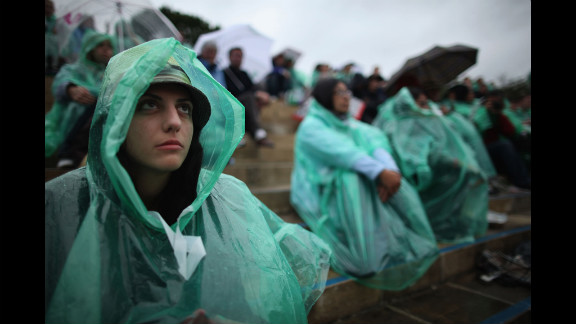 Tennis fans shield themselves from rain at Wimbledon on Monday.