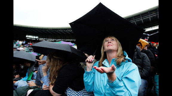 A spectator checks for rain, as rain delays halt play at the Wimbledon championships in London on Tuesday.