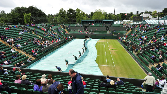 Ground staff workers remove covers from the grass before the start of the fourth round men