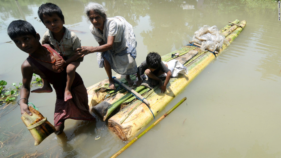 An old lady with her grandchildren climbs off a banana raft in Jhargoan village in Morigoan district on June 29. The flooding has been described as the worst in recent times.