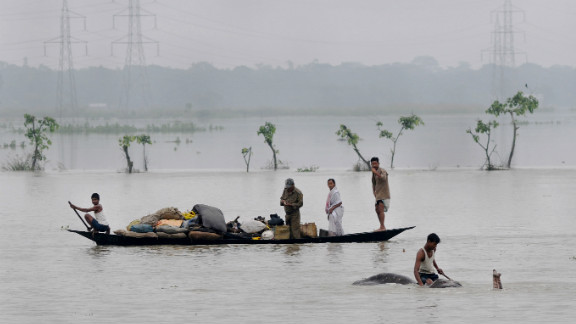 Villagers padddle with their belongings through flood waters in the Pobitora Wildlife Sanctuary, 55 kms from the capital city of the northeastern state of Assam on June 28, 2012. Floodwaters have submerged 90% of the sanctuary.