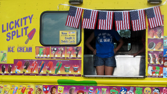An employee of the Lickity Split ice cream truck waits for customers during the parade in Centerville, Texas.